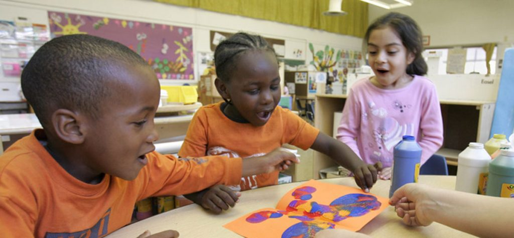 Children joyful and creating art together in a classroom