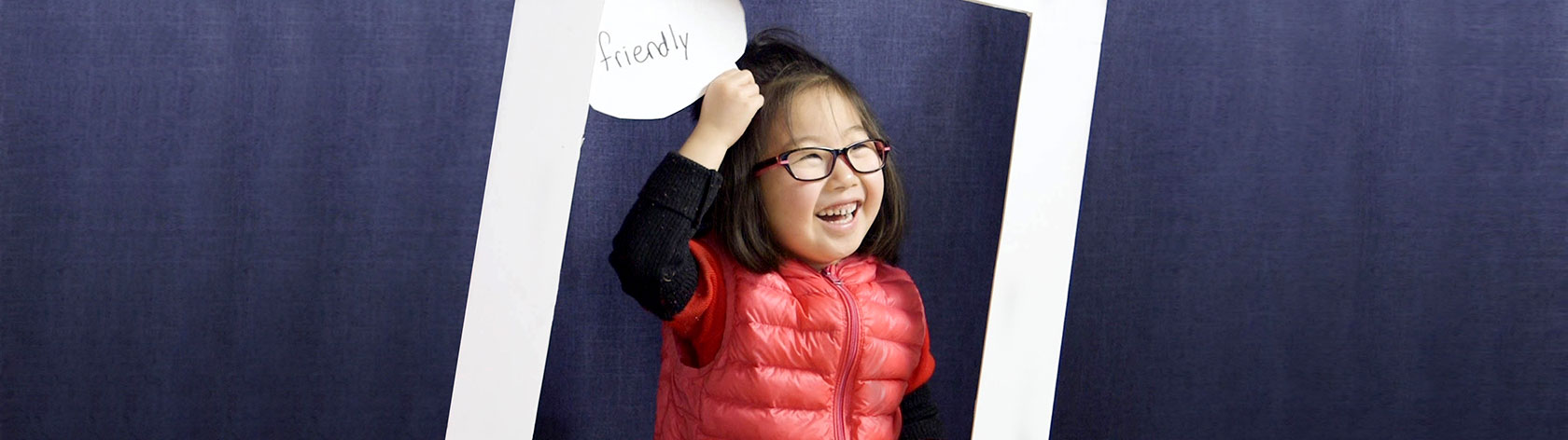 "Child smiling and holding up a card with the word ""friendly"""