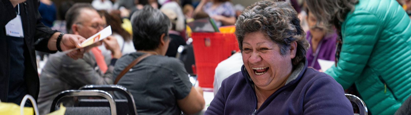 Joyful attendee laughs with fellow attendees at table