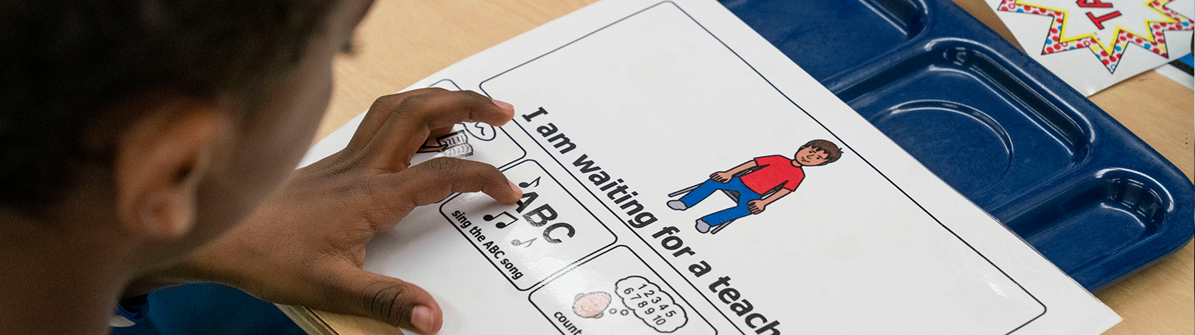 Picture of a child looking at a visual chart providing choices of what he can do while he waits for a teacher.