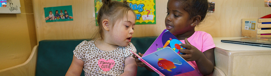 Two girls sit together on a couch reading board books together.