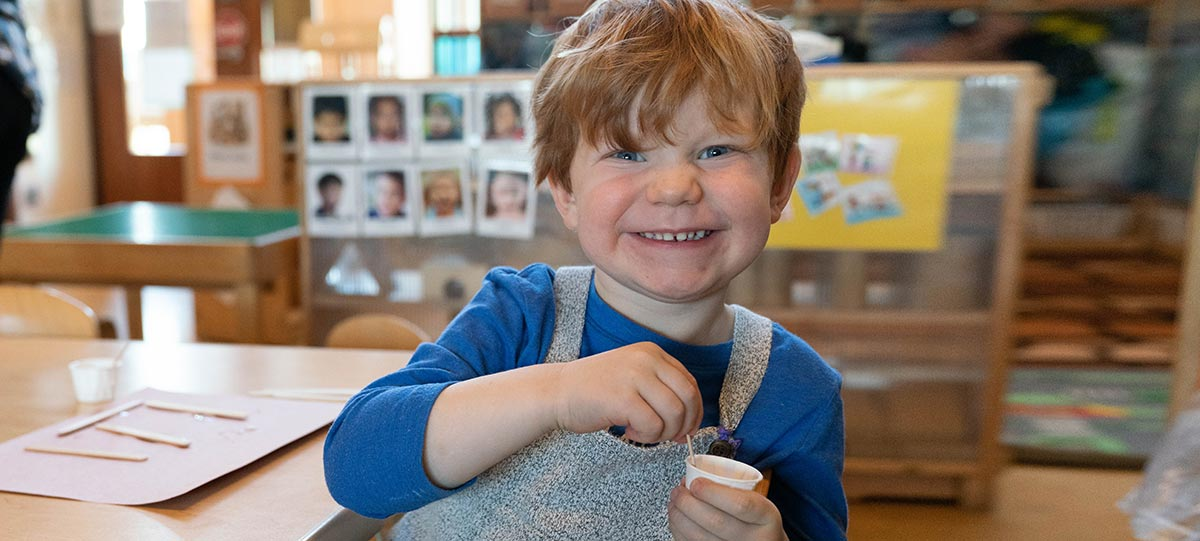 A child appears happy as they smile at the camera. The child appears to be sitting at a table, engaging in an Popsicle, and glue stick art activity.